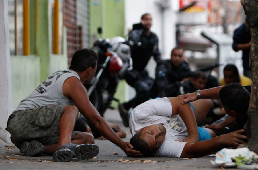 A resident bottom center who was shot lies on the ground as others help him during a police operation at the Grota slum in Rio de Janeiro Brazil on Friday Nov  26 2010  AP PhotoFeli 900x593 ワールドカップで潤うのは悪人も同じ!ブラジルマフィアは収益増。